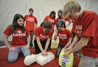 students in red shirts doing cpr training