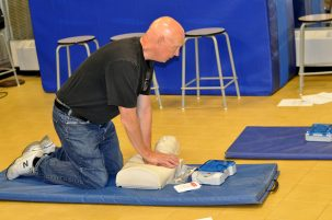 teacher doing cpr training in gym